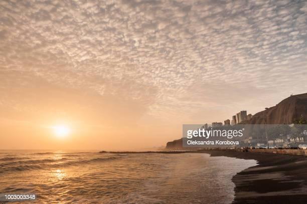 the beach along the cliffs of miraflores neighborhood in lima peru. peaceful seaside by the pacific ocean at sunset. - lima peru fotografías e imágenes de stock