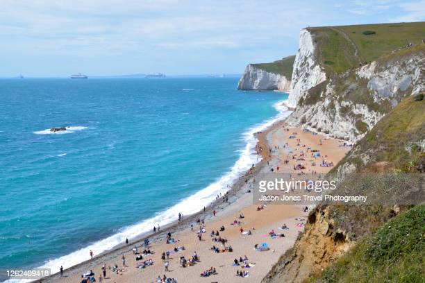 the beach at durdle door full of people relaxing - dorset uk stock pictures, royalty-free photos & images