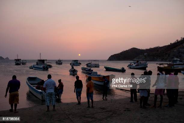 The beach at dusk sunset in Taganga with silhouetted fishing boats coming in to land after a day at sea Santa Marta district Colombia