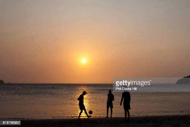 The beach at dusk sunset in Taganga with silhouetted people young men playing football as the sun goes down Santa Marta district Colombia