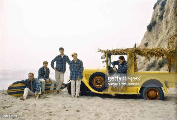 The Beach Boys (L-R Mike Love, David Marks, Brian Wilson, Dennis Wilson and Carl Wilson Pose with a surf board and truck on the beach in August 1962...