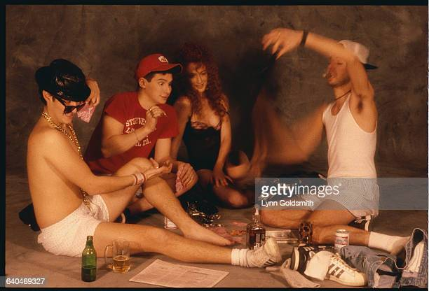 The Beastie Boys play strip poker and drink beer with a young woman in a black negligee