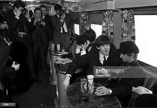 The Beatles 1964 US Tour 11th February British pop group The Beatles have their pictures taken by a group of photographers as they sit at a table...