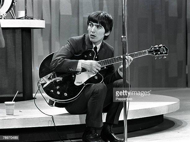 The Beatles 1964 US Tour Guitarist George Harrison of the British pop group The Beatles holding his instrument while sitting on stage during their...