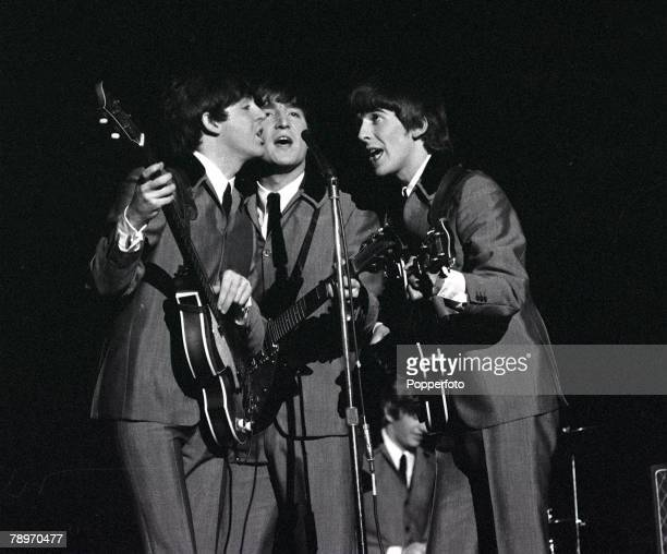Paul McCartney John Lennon and George Harrison share a microphone as they sing a song in concert at Carnegie Hall in New York during the band's tour...