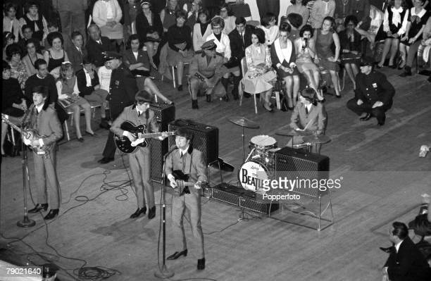 The Beatles 1964 US Tour Paul McCartney John Lennon and George Harrison of the British pop group The Beatles singing on stage during one of two...