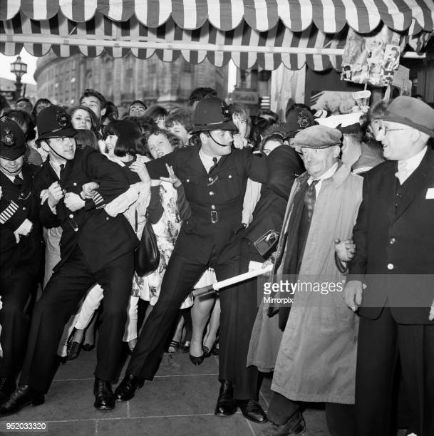 The Beatles A Hard Day's Night royal film premiere at the London Pavillion Theatre in Piccadilly Circus London Police trying to restrain crowds...