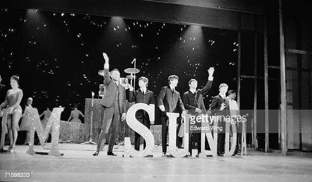 The Beatles and compere Bruce Forsyth wave farewell from the centre stage revolve at the end of the 'Sunday Night at the London Palladium' television...
