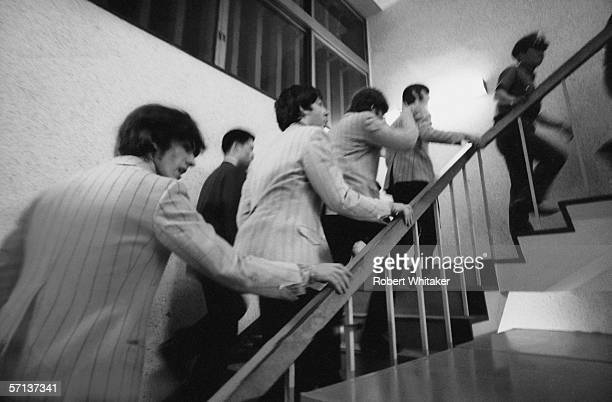 The Beatles are escorted to the stage of the Nippon Budokan for a matinee concert during their Asian tour 2nd July 1966
