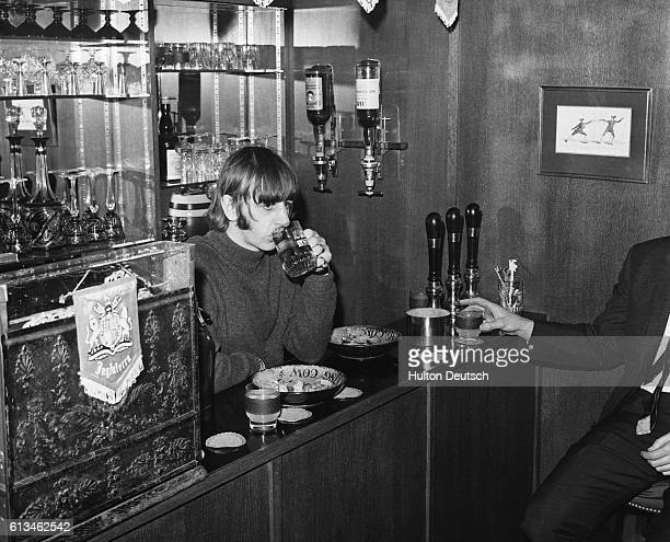 The Beatles drummer Ringo Starr enjoys a drink at his home in Surrey in the room which he has converted to a bar with on tap beer and a till circa...