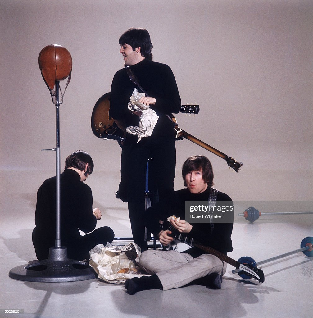 The Beatles eat fish and chips during the making of a promotional film for their single 'I Feel Fine', February 1966. Left to right: John Lennon (1940 - 1980), Paul McCartney and Ringo Starr.