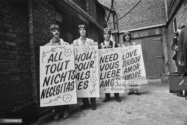 The Beatles hold up sandwich boards in different languages during the Our World satellite broadcast of the song 'All You Need is Love' from Abbey...