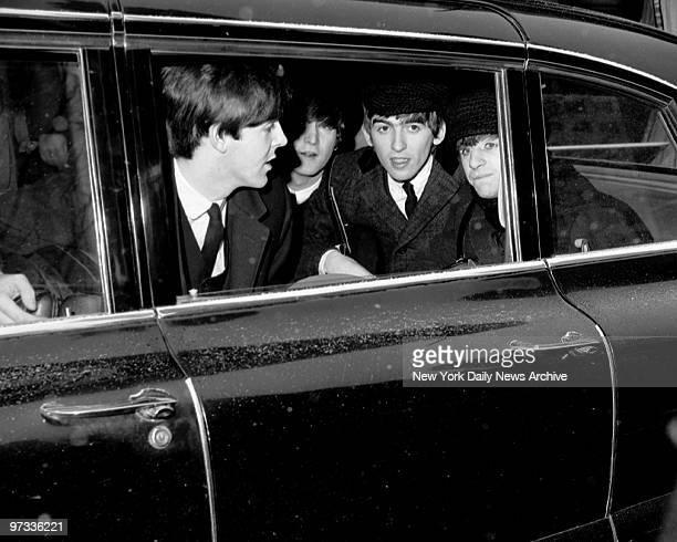 The Beatles huddle in back of limousine en route to Penn Station after concert appearance on Ed Sullivan Show That's Paul McCartney John Lennon...