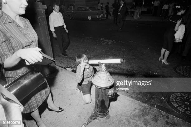 The Beatles in New York City on their North American Tour a head of their concert to be held at Forest Hills A young fan looking though a telescope...