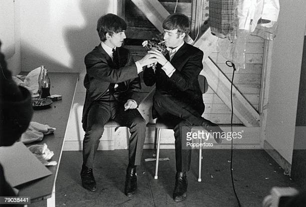 The Beatles in Stockholm Sweden John Lennon has his cigarette lit by George Harrison in their dressing room prior to a Swedish TV show
