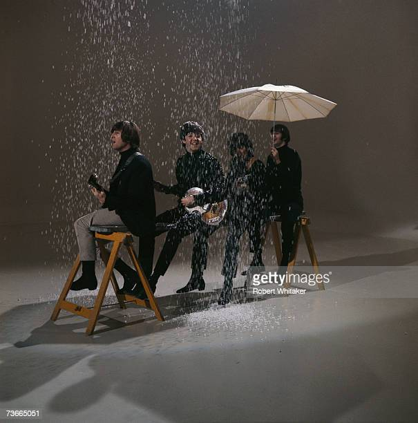 John Lennon Paul McCartney George Harrison and Ringo Starr sitting on a trestle under a simulated snow shower during the making of a promotional film...