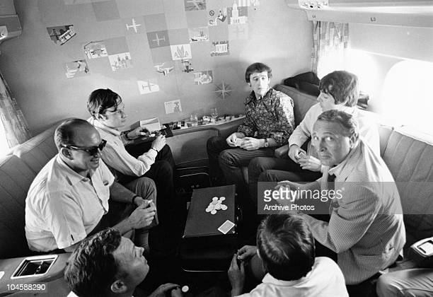 The Beatles' manager Brian Epstein Beatles singer Paul McCartney and others play a game of cards aboard an airplane during a tour circa 1960s