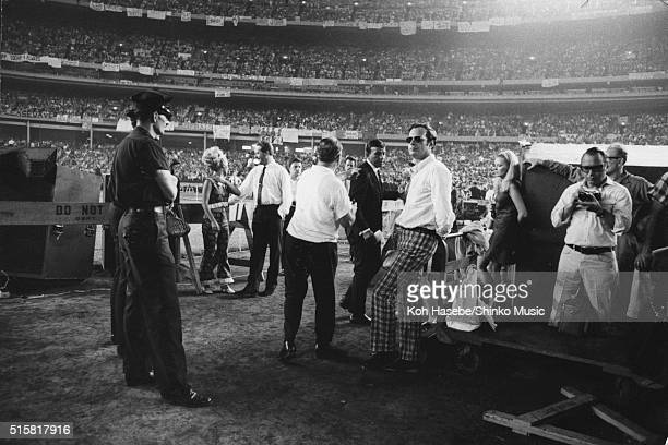 ?The Beatles' manager Brian Epstein stands in front of the stage watching as the band perform at Shea Stadium, New York, August 23, 1966. ?