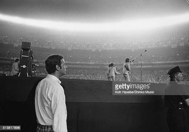 The Beatles' manager Brian Epstein watches from the side of the stage as the band perform at Shea Stadium, New York, August 23, 1966.