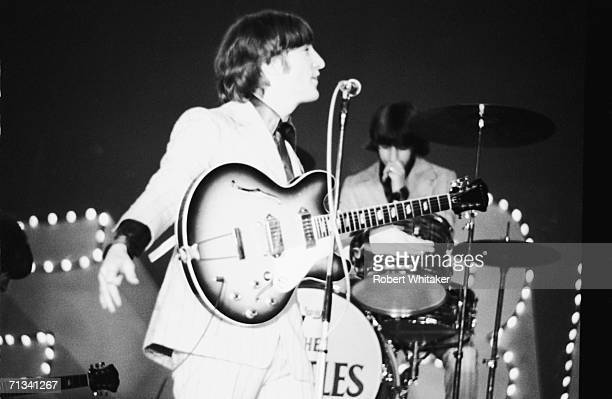 The Beatles on stage at Tokyos Budokan Hall Ringo Starr on drums in the background and John Lennon Japan 1st July 1966