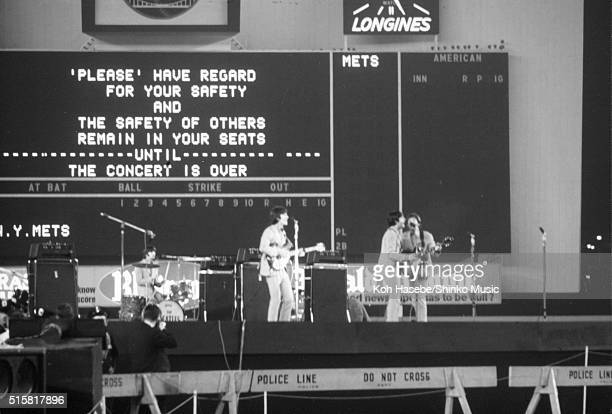 The Beatles perform in front of a sign asking the audience to remain in their sest till the end of the show at Shea Stadium New York August 23 1966...