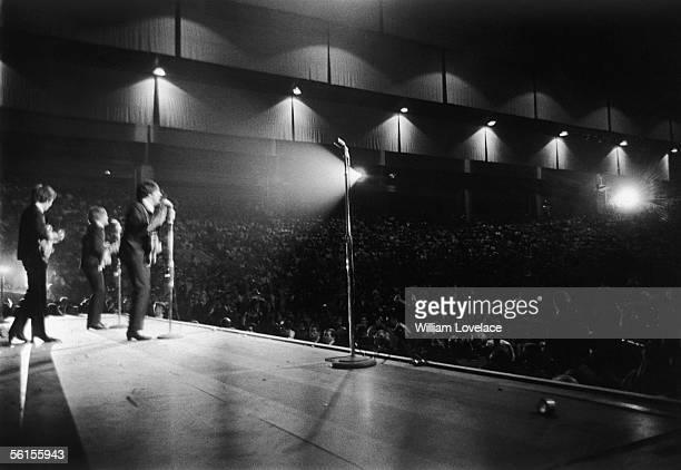 The Beatles perform on stage to a crowded venue during the groups tour of America August 1964