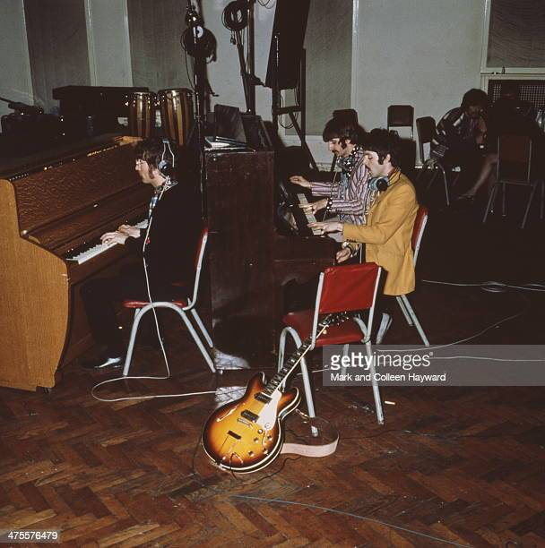 The Beatles play pianos at Abbey Road Studios London circa 1967 Left to right John Lennon Ringo Starr and Paul McCartney George Harrison is sitting...