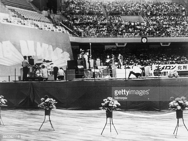 The Beatles playing in Budokan Japan surrounded by flowers June 1966