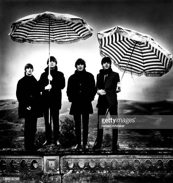 The Beatles pose for a group portrait holding striped umbrellas at a hotel in Perthshire Scotland 1964 Left to right Ringo Starr John Lennon George...