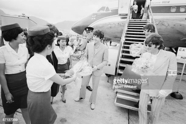 The Beatles receive welcome bouquets from the staff at Hong Kong International Airport during their Asian tour 3rd July 1966 Their aircraft stopped...