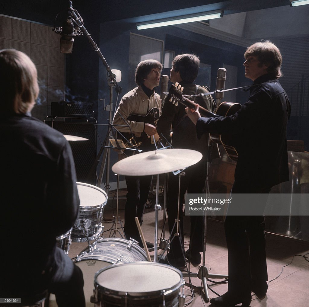 The Beatles rehearse; from left to right, Ringo Starr with his back to the camera, George Harrison (1943 - 2001) at the microphone with Paul McCartney and John Lennon (1940 - 1980).