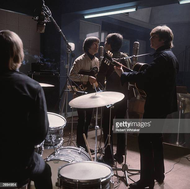 The Beatles rehearse from left to right Ringo Starr with his back to the camera George Harrison at the microphone with Paul McCartney and John Lennon