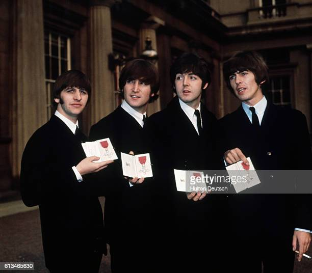 The Beatles Ringo Starr John Lennon Paul McCartney and George Harrison show off their MBE medals after their investiture at Buckingham Palace