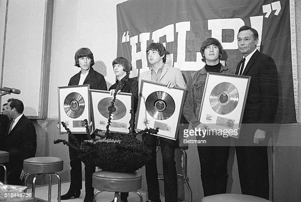 The Beatles show off their golden records during a news conference for the 1965 film Help!. From left to right: George Harrison, Ringo Starr, Paul...