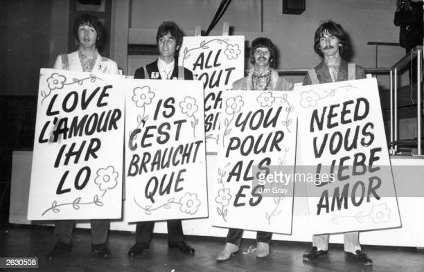 The Beatles sporting multilingual 'Love Is All You Need' sandwich boards at the EMI studios in Abbey Road as they prepare for 'Our World' a worldwide...
