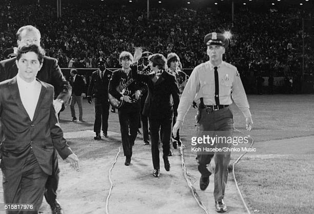The Beatles walking to the stage Ringo Starr waving to the fans during the last show of their final tour at Candlestick Park San Francisco California...