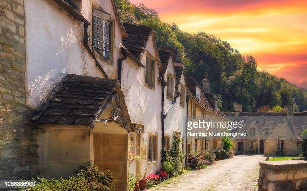 the beautiful bibury village under the sunlight from the colorful sky shows the ancient little houses in uk. - village stock pictures, royalty-free photos & images