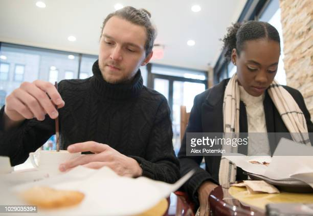 The beautiful Black young woman and the handsome White man eating in the small cafe