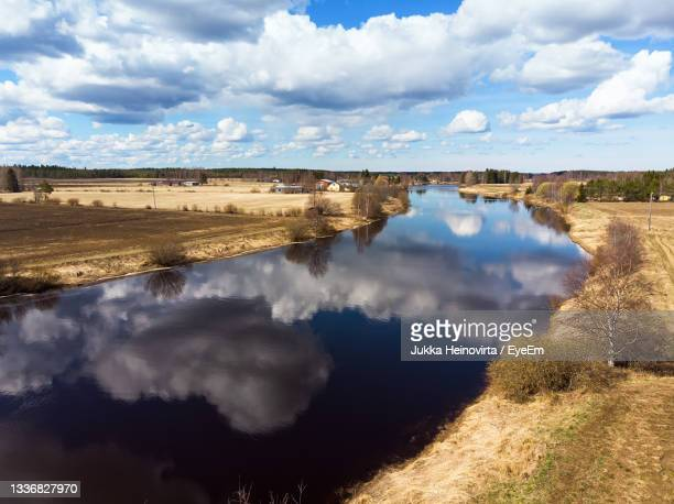 the beautiful clouds reflect on the still water of the river at the rural finland. - heinovirta stock pictures, royalty-free photos & images