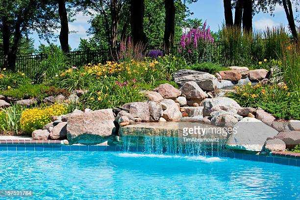 the beautiful poolside of a waterfall with rocks - landscaped stock pictures, royalty-free photos & images