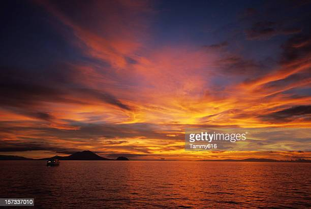 the beautiful warm hues in the sky above a ocean horizon - papua new guinea stock pictures, royalty-free photos & images