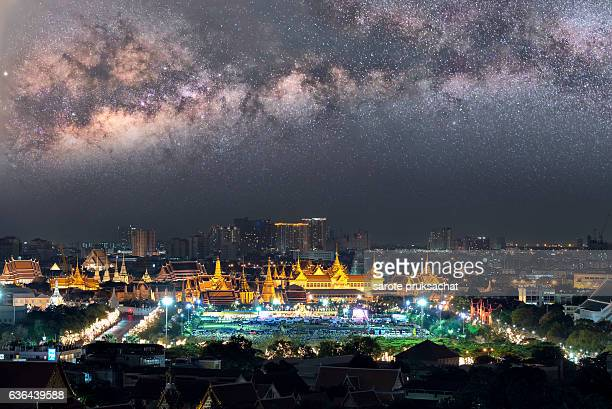 The beauty of the Emerald Buddha Temple at Milky way galaxy with stars and space dust in the universe.