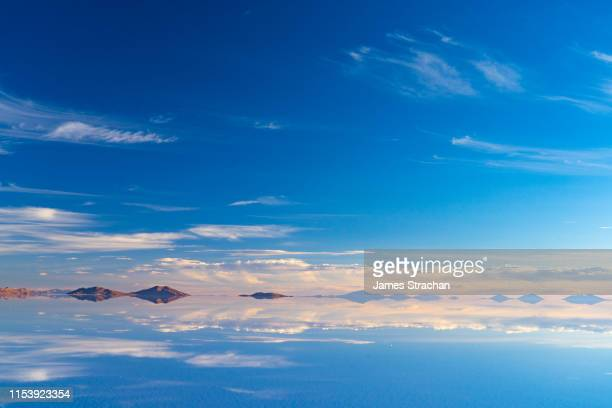 the beauty of the salt flats which are reflecting the clouds and mountains after rainfall as the sun sets, uyuni, bolivia - ウユニ塩湖 ストックフォトと画像