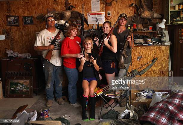 The Becker family including Darren his wife Dorthy and their children Renee 15 Katie 17 and Charlie show off a small part of the family weapons...