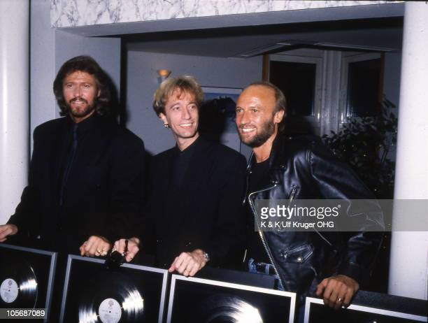 The Bee Gees LR Barry Gibb Robin Gibb and Maurice Gibb being presented with gold discs in 1991 in Germany