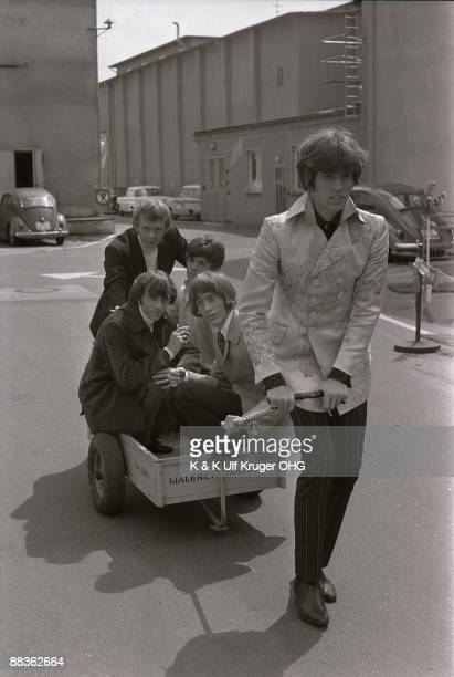 The Bee Gees pose for a group shot with Barry Gibb pulling Maurice Gibb Colin Petersen Vince Melouney and Robin Gibb in a wagon outside a TV studio...