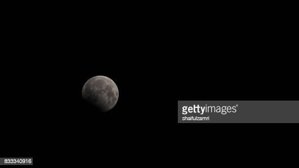 the beginning of the lunar eclipse in kuala lumpur on 8th august 2017 - luna nera foto e immagini stock