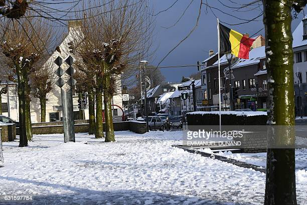 The Belgium flag fluters in the wind over a snow-covered square in Waterloo on the outskirt of Brussels on January 13 following an overnight snow...