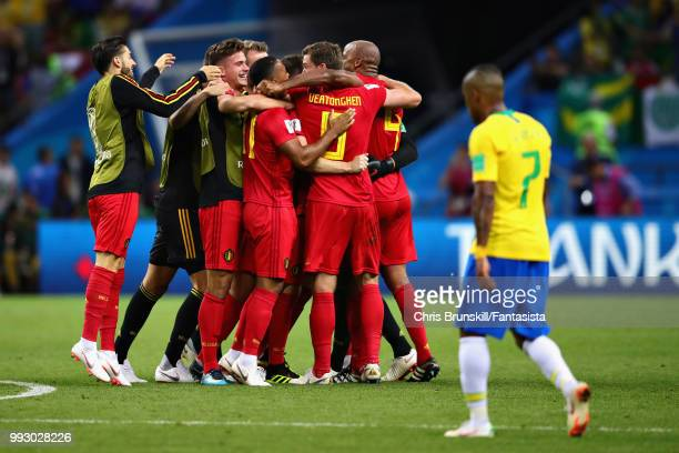 The Belgium team celebrate as Douglas Costa of Brazil looks dejected after the 2018 FIFA World Cup Russia Quarter Final match between Brazil and...