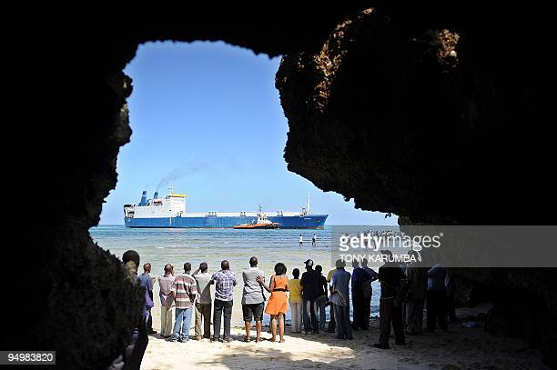 The Belize flagged MV Faina is escorted on February 12 2009 into the port of Mombasa by a Kenya Ports Authority tugboat as people gather to witness...